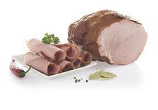 Piece of ham with leaf and slices on plate. Isolated on a white Royalty Free Stock Image