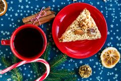 Piece of handmade apricot pie on red plate and red cup with tea or coffee with fir tree, pines, cinnamon on blue placemat royalty free stock photo