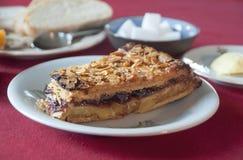 Piece of handmade cake with almonds, jam, cream Royalty Free Stock Image