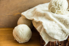 Piece of handmade knitwear, clew of white wool yarn on vintage hobby and crafts wicker chest, wood table, cozy. Atmosphere, shabby chic style royalty free stock photos