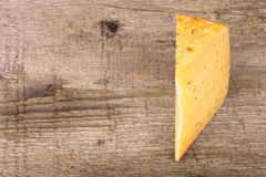 Piece hard cheese with herbs on an old wooden table Royalty Free Stock Photos