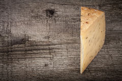 Piece hard cheese with herbs on an old wooden table. Tinted with Stock Photo