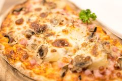 Pieces of hawaiian pizza with pineapple, mushroom and ham ingredients on wooden board stock photos