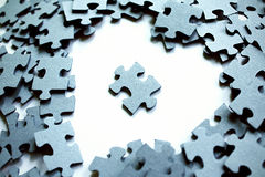 Piece in Heart. A unique puzzle piece isolated in the empty space in the shape of a heart, amongst other puzzle pieces Stock Photo