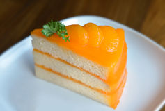 Piece of home made orange cake. In coffeeshop with day light Stock Photos