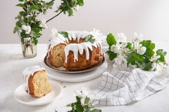 Piece of homemade apple pie with white icing and flying petals of flowering apple branches on white background. Pastry. Festive stock images