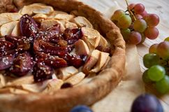 A piece of the homemade apple plums pie decorated with fresh grapes, plums, brown raisins and sesame on light wooden background. Close up view Stock Photos