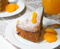A piece of homemade apricot pie on the white plate. A piece of apricot pie, decorated by dried apricots on the white plate. Orange juice in the background.The royalty free stock photography