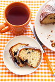 Piece of homemade bundt cake on plate with orange mug Royalty Free Stock Image