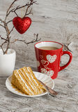 Piece of homemade cake, a mug of tea and a red heart on rustic light wooden table. Valentine's day romantic breakfast. Royalty Free Stock Image