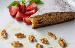 Piece of homemade cake. A piece of homemade cake with strawberry decoration and nuts Royalty Free Stock Photography
