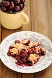 Piece of homemade cherry crumble with fork and yellow metal cup Stock Image