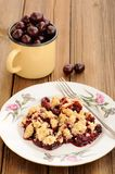 Piece of homemade cherry crumble with fork and yellow metal cup Royalty Free Stock Images