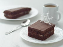 Piece of homemade chocolate cake decorated with sugar snowflake. Chocolate brownies arranged on white plate. Christmas treat. Selective focus on the snowflake Royalty Free Stock Images