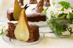 Piece of homemade chocolate cake with pears decorated pear blossom Royalty Free Stock Images
