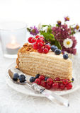Piece of homemade honey cake decorated with fresh berries. Piece of homemade honey cake decorated with fresh blueberries and red currants Stock Image