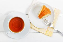 Piece of homemade lemon cake and cup of tea on white wooden tabl stock image