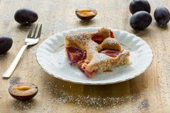 Piece of homemade plum pie on a white plate with organic plums and fork on wooden table. Closeup royalty free stock photography