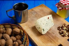 Piece of homemade spicy cheese with walnuts,mug of homemade wine. Piece of homemade spicy cheese ready to slicing, served with walnuts,mug of homemade wine and Stock Images