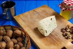 Piece of homemade spicy cheese with walnuts,mug of homemade wine. Piece of homemade spicy cheese ready to slicing, served with walnuts,mug of homemade wine and Royalty Free Stock Photos
