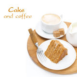 Piece of honey cake, cream, cup of cappuccino on wooden board Stock Photos