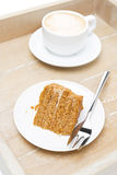 Piece of honey cake and cup of cappuccino on a wooden tray Royalty Free Stock Photos
