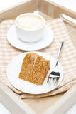 Piece of honey cake and cup of cappuccino on a wooden tray Royalty Free Stock Photography