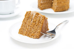 Piece of honey cake  and fork on white plate Stock Images