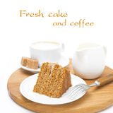 Piece of honey cake, fresh cream and coffee on wooden board Royalty Free Stock Images