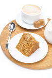Piece of honey cake, jug of cream and cup of cappuccino Royalty Free Stock Images