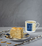 A piece of honey cake. On the plate, cup with lemon tea in background Royalty Free Stock Photo