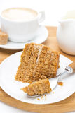 Piece of honey cake on a plate, fork and cup of cappuccino Royalty Free Stock Images
