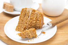 Piece of honey cake on a plate and fork on wooden board Stock Image