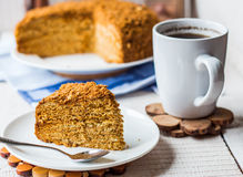 A piece of honey cake with sour cream and nuts Stock Photos