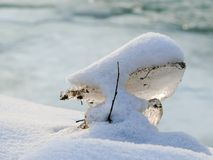 Piece of ice covered with fluffy snow during winter time royalty free stock photo
