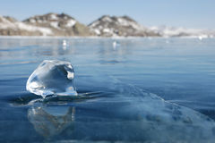 Piece of ice on the frozen lake. Transparent piece of ice on the mirrored surface of frozen lake. Low depth-in view Stock Photos