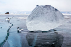 A piece of ice on the surface of the blue frozen Lake Baikal with car at background Stock Photo