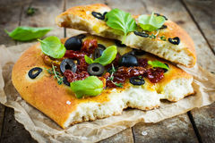 Piece of Italian focaccia bread with black olives, dried tomatoe Royalty Free Stock Images