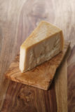 Piece of italian parmesan cheese on wooden cutting board Royalty Free Stock Photos