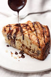 A piece of Italian Polenta apple cake being dripped with chocolate sauce. Stock Photos
