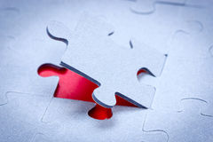 Piece of jigsaw revealing red background Stock Images