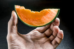 Piece of juicy melon holds men's hand on a dark background Stock Photography