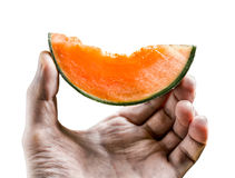 Piece of juicy  melon holds men's hand isolated on white backgro Stock Photo