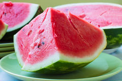 A piece of juicy ripe watermelon with fleshy pink flesh on a lig Stock Photography