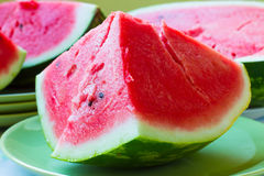 A piece of juicy ripe watermelon with fleshy pink flesh on a lig Stock Photos