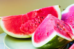 A piece of juicy ripe watermelon with fleshy pink flesh on a lig Royalty Free Stock Photos