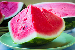A piece of juicy ripe watermelon with fleshy pink flesh on a lig Royalty Free Stock Photo