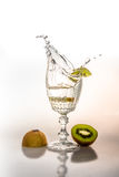 Piece of Kiwi falling in a glass. Of champagne Stock Images