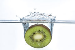 Piece of a kiwi falling into water with a splash. Piece of a kiwi falling into water with a big splash Royalty Free Stock Photos