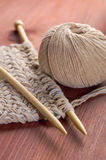 Piece of knitted cloth with threads and wooden needles on wooden table Stock Photos